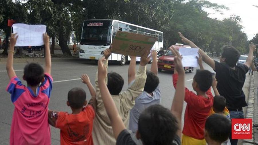 Terlihat anak-anak sedang menunggu setiap bus yang lewat dan bersorak meminta dibunyikan klakson