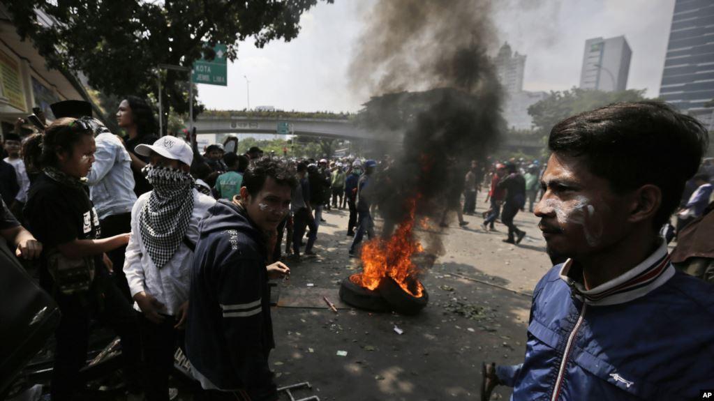 Para pengunjuk rasa beristirahat dekat sebuah ban yang terbakar setelah bentrok dengan polisi dalam demonstrasi memprotes hasil rekapitulasi pilpres di Jakarta, Rabu, 22 Mei 2019. (Foto: AP via VOA Indonesia/Dita Alangkara)