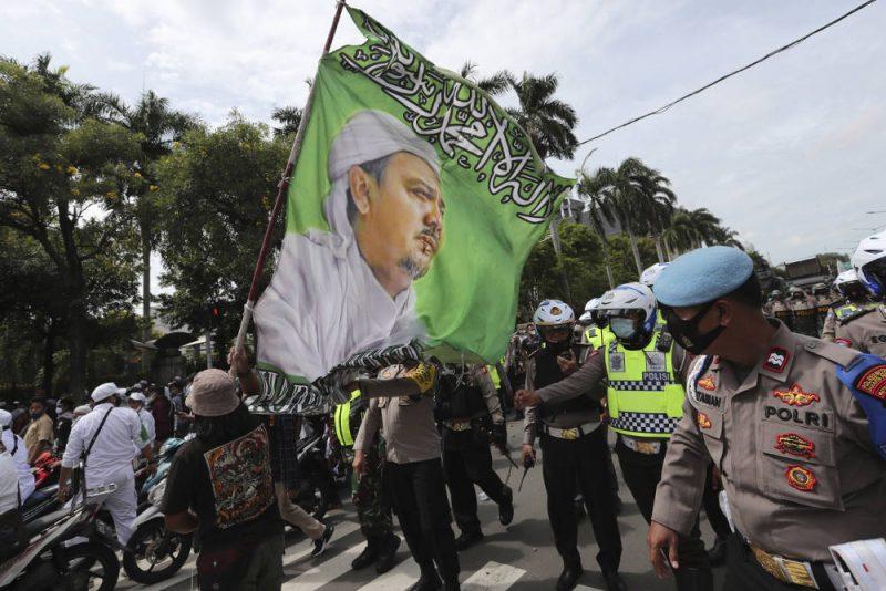 Para pendukung Muhammad Rizieq Shihab, Pimpinan Front Pembela Islam (FPI), sambil membawa bendera besar bergambar ulama kontroversial itu melakukan unjuk rasa di Jakarta 18 Desember 2020 (AP Photo/Tatan Syuflana via BenarNews.com)