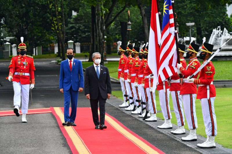 Presiden Joko Widodo dan Perdana Menteri Malaysia Muhyiddin Yassin memeriksa barisan kehormatan di Istana Kepresidenan, di Jakarta, 5 Februari 2021. (AFP via BenarNews.org)