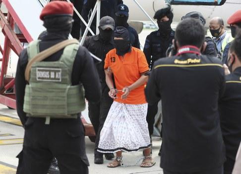 Polisi mengawal tersangka salah satu pimpinan jaringan Jemaah Islamiyah, Zulkarnaen (tengah), yang juga dikenal sebagai Aris Sumarsono, setibanya di Bandara Internasional Soekarno-Hatta di Tangerang, Banten, 16 Desember 2020. [AP]